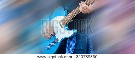 Guitarist Man In Jeans Playing Music On Blue Electric Guitar. Sides Of Image Blurred With Motion Blu