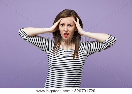 Perplexed bewildered young brunette woman in casual striped clothes posing isolated on violet purple background studio portrait. People lifestyle concept. Mock up copy space. Putting hands on head. poster