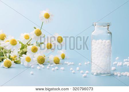 Homeopathic Globules And Glass Bottle On Blue Background Next To Medicinal Chamomile Flowers.
