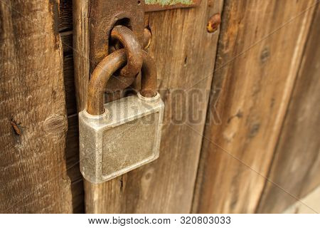 Old Rusty Squre Padlock Hanging On Natural Brown Wooden Door