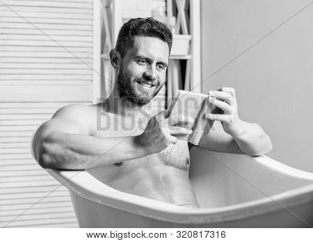 Sexy Man In Bathroom Reading. Macho Naked In Bathtub. Sex And Relaxation Concept. Man Has Muscular B