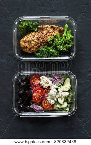 Two Healthy Balanced Lunch Boxes With Greek Salad, Baked Chicken Breast And Broccoli On A Dark Backg