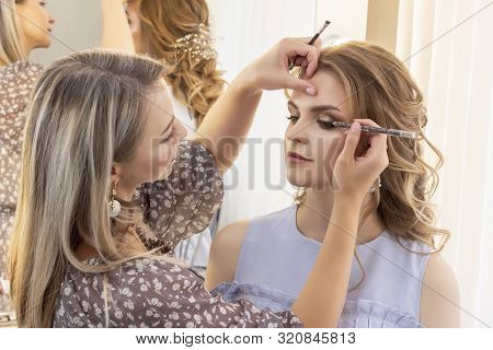 Makeup Artist Puts Make Up On Girl Model. Wedding Makeup, Evening Makeup, Natural Makeup. Make-up Ar
