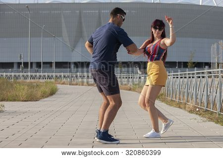 Young Couple Dancing Latino Dance Against Urban Landscape.