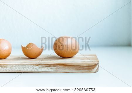 Close Up Of Brown chicken egg and eggshells over a wooden board poster