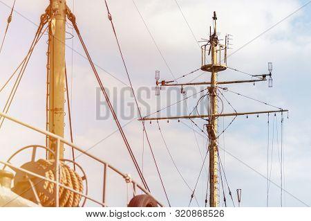 Ship mast of frigate, longboat or navy battleship. Metal mast pole. Ship awaits captain at docks. Lowered sails, blue sky on background. poster