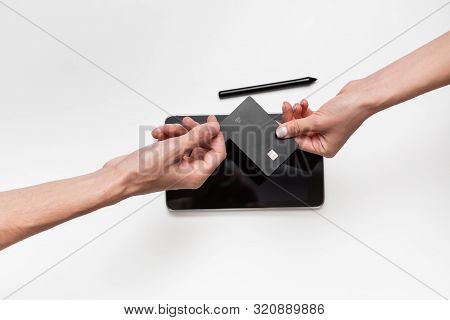 Close Up Top View Of A Woman Hands Over Bank Card To A Man In Order To Pay For The Product. Tablet A