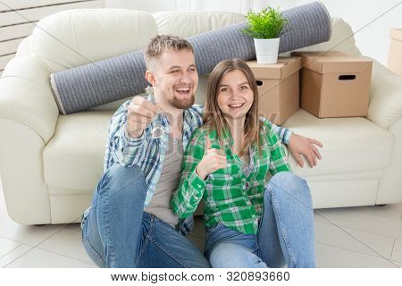 Young Positive Couple Holding Keys To A New Apartment While Standing In Their Living Room. Housewarm
