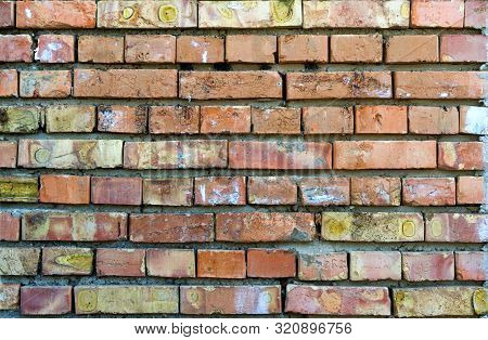 A Wall Of Bricks, Roughly Laid Out With Heterogeneous Spots And Cracked Paint