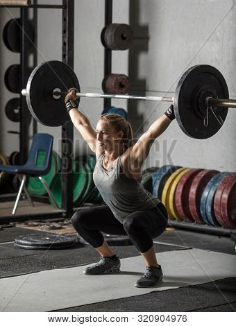 Young, strong, female weight lifter practicing snatch in weight room with heavy barbell.