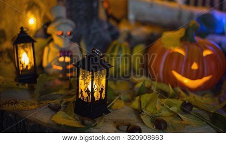 Halloween Decorations Concept At Night. Close Up Of Jack O'lantern, Vintage Lanterns, Pumpkins, Skul