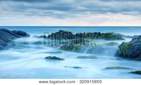 Long Exposure Of Mystery Ocean And Rocks. Tropical Landscape With Surreal Stones On Sea Beach. Sceni