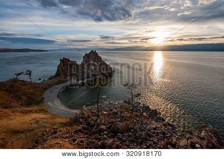 Sunset On Lake Baikal Overlooking The High Cliff Of Shamanka And Beautiful Sky. There Are Stones And