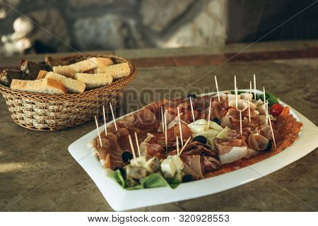 Plate With Various Meat Snacks And Cheese. In The Background Is A Plate Of Bread.