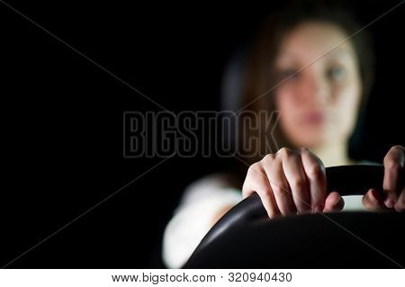 The Girl In The Background In Defocus Holds The Steering Wheel With Her Hands. Night, The Girl In Th