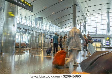 Doha Qatar - July 13 2019; Passengers Waiting In Line With Baggage  Ready To Board Plane As Peopson