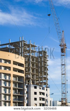poster of Tower crane working on a house construction. Blue sky background