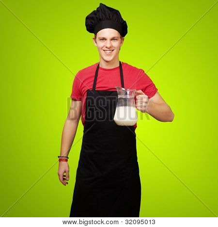 portrait of a young cook man holding a milk jar over a green background