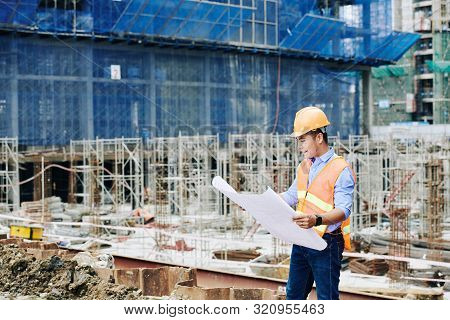 Smiling Vietnamese Construction Engineer Checking Blueprint Before Starting New Day Of Work