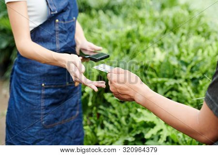 Customer Giving Credit Card To Greenhouse Worker To Pay For The Plants He Has Chosen