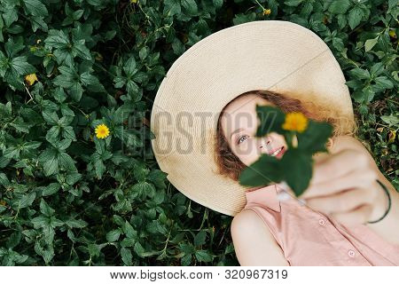 Pretty Young Wman With Beautiful Blue Eyes Lying On Grass, Looking At Camera And Outstretching Hands