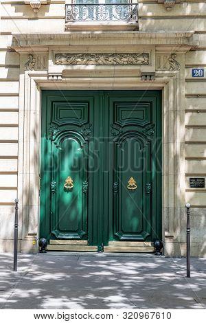 Paris / France - 06 26 2019: Entrance With Framed Door Painted In Emerald Green Color. Elegant Doorw