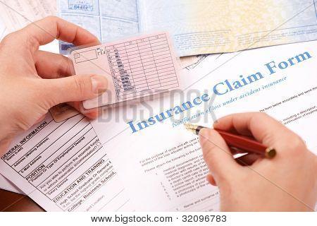 Hand Versicherungsanspruch Formular ausfüllen. Andere Zeitungen wie ID oder Fahrzeug Dokumente im Hintergrund