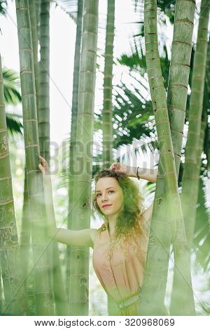 Calm Beautiful Young Caucasian Woman Resting In Bamboo Forest And Feeling Commune With Nature