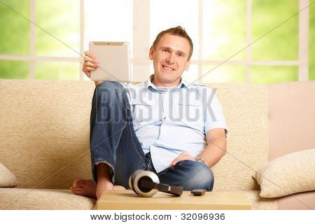 Man using tablet, sitting on sofa in home with big window in background, headphones on table