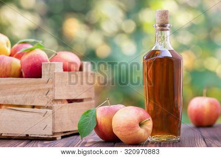 Apple Cider Or Vinegar In Glass Bottle And Ripe Fresh Apples On Wooden Table Outdoors