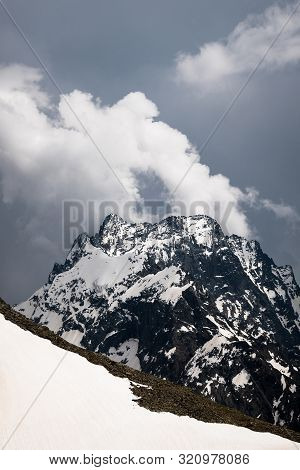 View Of A High Steep Rocky Mountain Partially Covered With Snow Against A Dark Cloudy Sky With Cloud