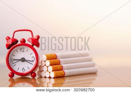 Cigarettes Stack And Red Alarm Clock. World No Tobacco Day. Cigarette And Family Figure. A Concept F