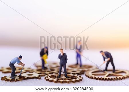 Miniature Businessman And Many Workers Standing On Wooden Gear. Income And Economic Inequality Conce