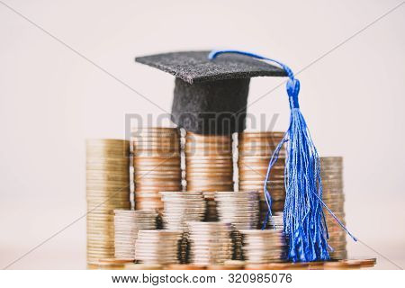 Graduation Hat On Coins Money On White Background. Saving Money For Education Or Scholarship Concept