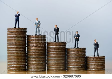 Small Businessmans Figures Standing On Tstack Of Coins. Time Is Money. Time Investment And Retiremen