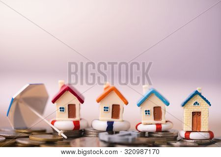 Home Insurance Concept. House Model In Lifebuoys On Coins Stack. Securing Large Value Of Home By App