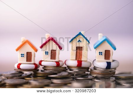 Home Insurance. House Model In Lifebuoys On Coins Stack. Securing Large Value Of Home By Applying An