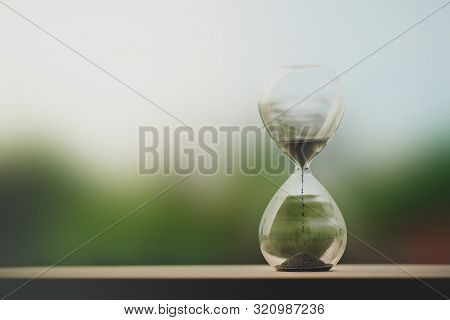 Hourglass On Table Concept For Time Slipping Away For Important Appointment Date. Time Passing Conce