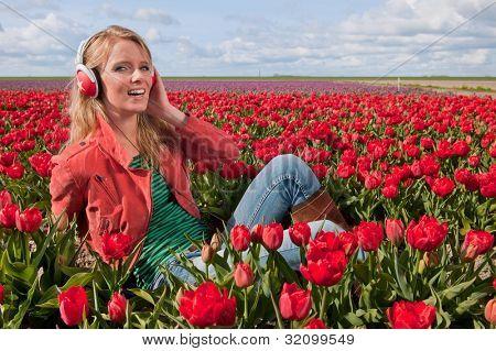 Mädchenbildnis schön blond niederländische Musikhören in Tulpen-Feld