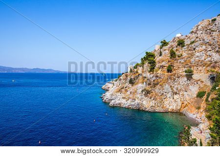 Beautiful Greek Landscape Of Avlaki Beach On Hydra With Tourists Floating In The Sea. Hydra Is One O