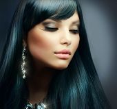 Beautiful Brunette Girl. Healthy Long Hair and Holiday Makeup. Jewelry poster