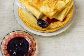 Stack of folded delicious freshly baked crepes with appetizing golden crust on white plate with homemade black current berry jam on linen table cloth. Cozy atmosphere poster