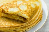 Stack of folded delicious freshly baked crepes with appetizing golden crust on white plate on linen table cloth by window in sunlight. Cozy atmosphere breakfast morning poster