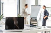 selective focus of two businesswomen standing near flipchart and laptops on table on foreground in office poster