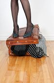 Woman in high heel shoes standing on leather suitcase overfilled with fashion clothing. poster