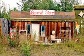 Old abandoned store with many articals out front. poster