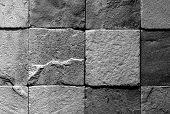 Black and white image of a section of wall made of roughly finished tiles poster