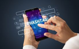 Female hand typing on smartphone with HASHTAG inscription, social media concept