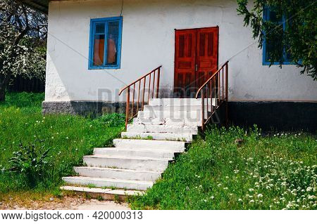 House With Red Door And White Staircase . House In Village With Walls Painted In White . Old Rustic
