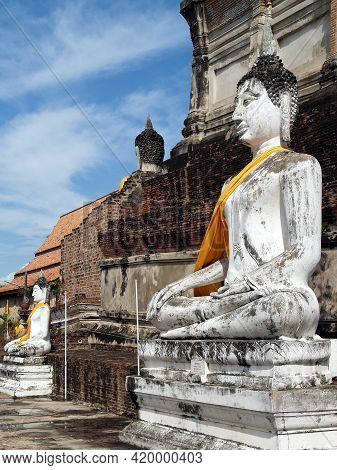 White Buddha Statues Around Ancient Brick Pagoda Of Wat Yai Chaimongkol (thai Temple) With Blue Sky,